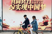 People ride shared bicycles on a Beijing street in April. (Nicolas Asfouri/AFP/Getty Images)