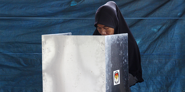 A woman votes at a polling station during an Indonesian regional election in June. (Aditya Irawan/NurPhoto via Getty Images)