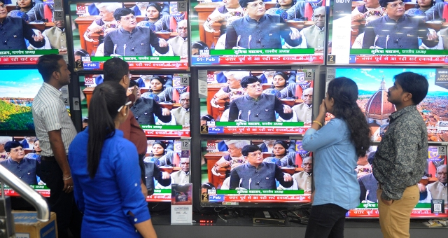 People at an electronics shop in Kolkata, India, watch as Finance Minister Piyush Goyal presents the country's interim budget on Feb. 1. (Samir Jana/Hindustan Times via Getty Images)