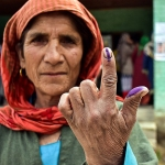 A woman shows her inked finger after voting in a village near Srinagar, India. (Saqib Majeed/SOPA Images/LightRocket via Getty Images)