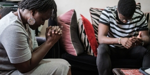 A mother and son pray at home during a live broadcast of an East Sunday service in Nairobi, Kenya. (Yasuyoshi Chiba/AFP via Getty Images)