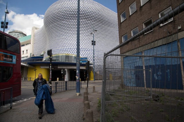 A homeless man carries his sleeping bag past the iconic Selfridges Building in Birmingham in 2017. (Mike Kemp/In Pictures via Getty Images)