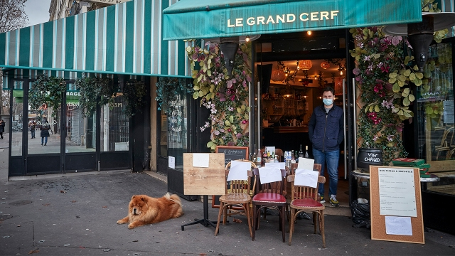 Owner Alexi Monen stands in the doorway of his Paris cafe selling a table and some chairs on Feb. 1, 2021. Restaurants in France have been closed to indoor dining since October. (Kiran Ridley/Getty Images)