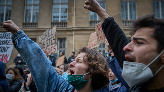 Protesters chant and demonstrate outside the French Senate in Paris, opposing a new law they say would consolidate police power and restrict civil liberties, on March 16, 2021. (Kiran Ridley/Getty Images)