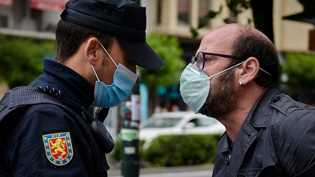 A pedestrian argues with a police officer in Pamplona, Spain, in May 2020. (Iranzu Larrasoana Oneca/NurPhoto via Getty Images)