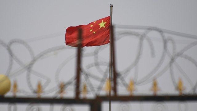 The Chinese flag flies behind razor wire at a housing compound south of Kashgar, China, in 2019. (Greg Baker/AFP via Getty Images)