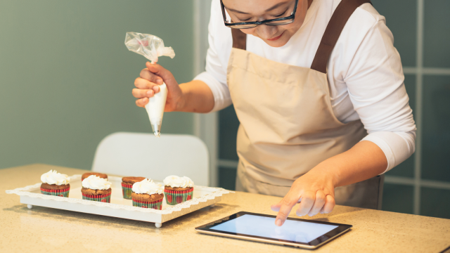 Chinese woman is decorates cupcakes and checks the recipe on iPad.