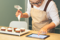 Chinese woman decorates cupcakes and checks the recipe on an iPad.
