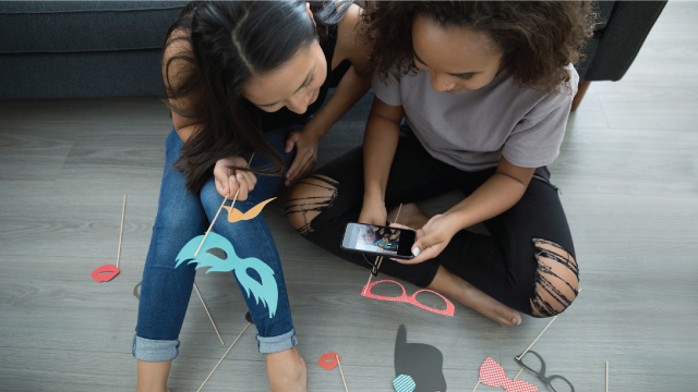 Teenage girl friends with props using camera phone on living room floor
