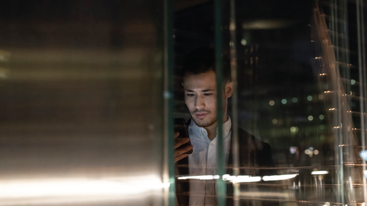 A photo of a young businessman in office building at night looking at smartphone, window view, Milan, Italy.