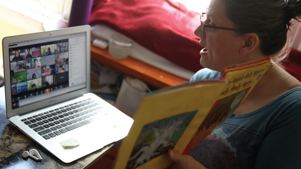 A first grade teacher in California conducts an online class from her living room.