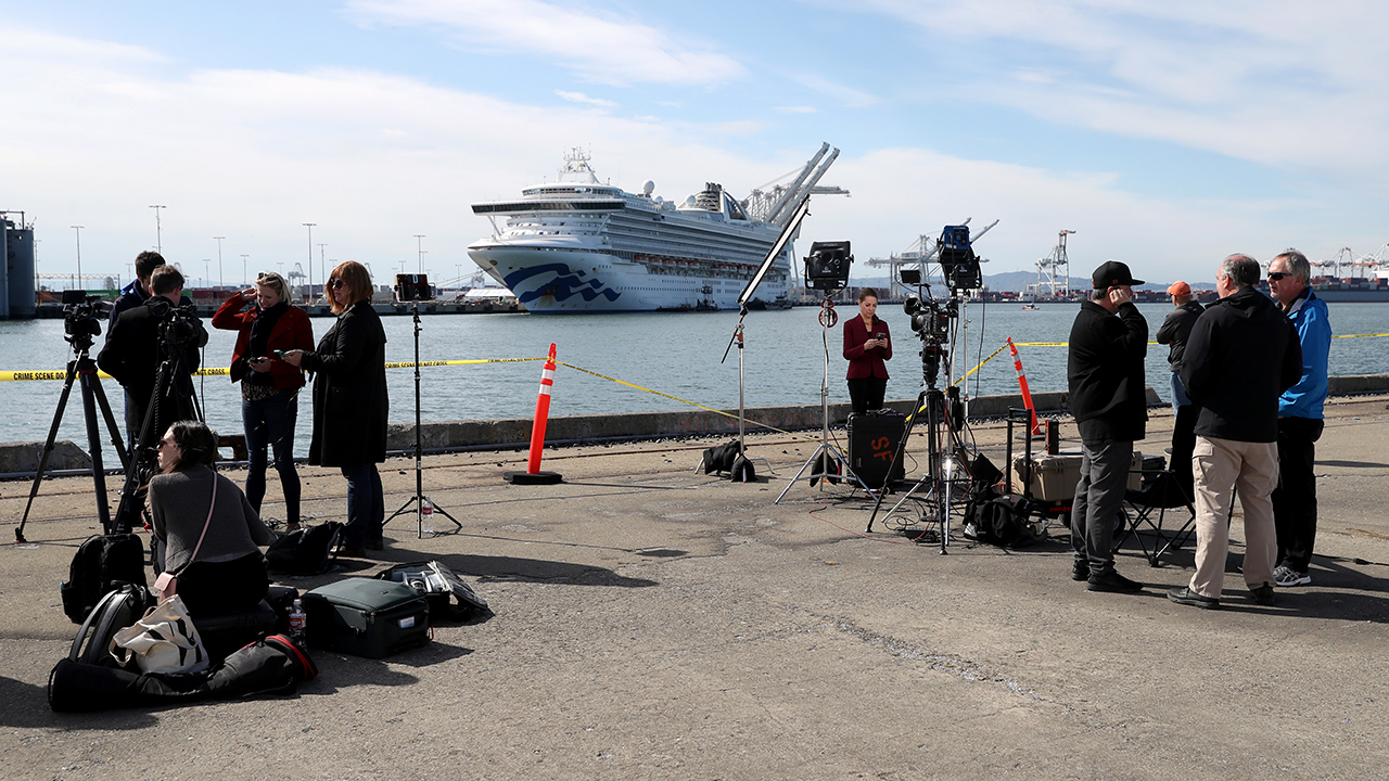 Journalists set up at the Port of Oakland, California, on March 10, across from the cruise ship Grand Princess. Passengers had begun to disembark after 21 people on board tested positive for COVID-19. (Justin Sullivan/Getty Images)