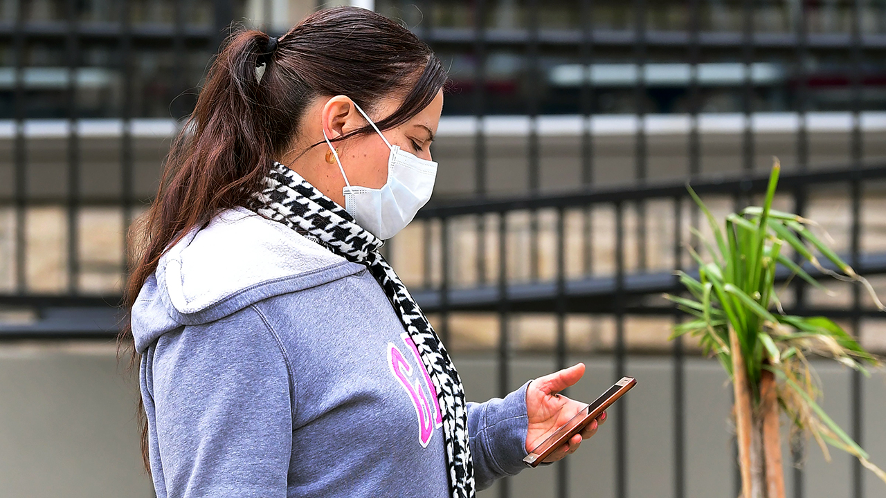 A woman checks her cellphone in Los Angeles on March 20. Los Angeles County had announced a near-lockdown a day earlier in an effort to slow the spread of the coronavirus. (Frederic J. Brown/AFP via Getty Images)