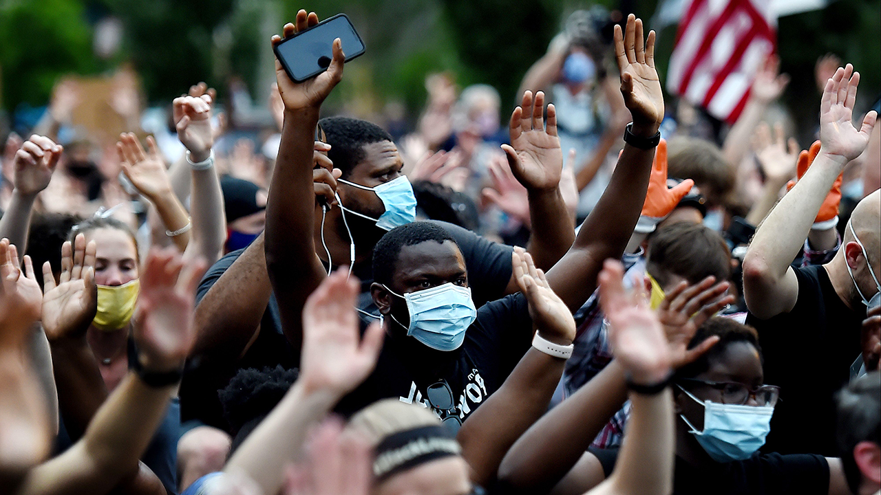Protesters kneel and hold up their hands in front of Lafayette park near the White House to protest the death of George Floyd, who died in police custody in Minneapolis on June 4, 2020 in Washington, DC. (Photo by OLIVIER DOULIERY/AFP via Getty Images)