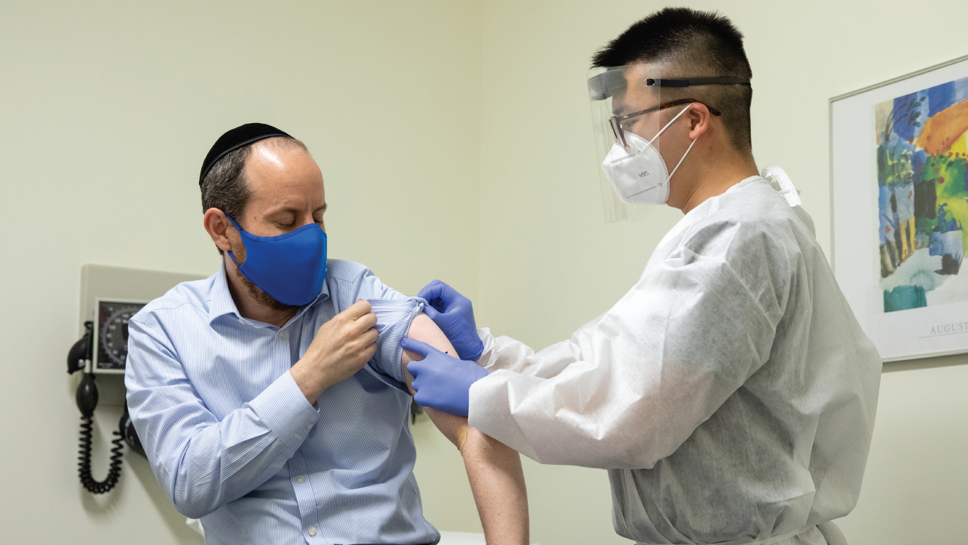 Rabbi Shmuel Herzfeld has his arm disinfected by Dr. Chao Wang during a clinical trial for a Coronavirus vaccine.(Amanda Andrade-Rhoades/Getty Images)