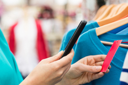 Photo of a shopper using a smart phone to price-compare clothing