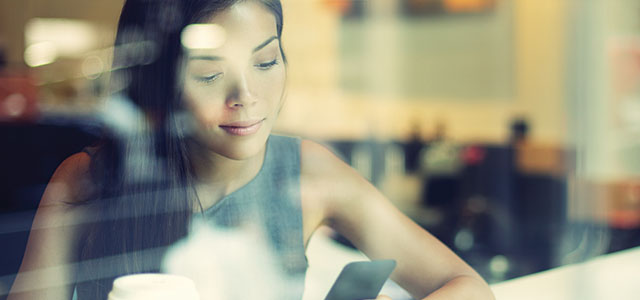 Woman using smart phone in coffee shop