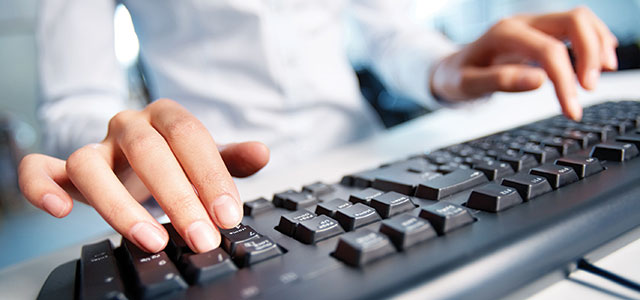 Closeup photo of hands on a keyboard