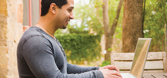 Young man using a laptop outside