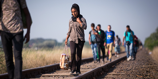 Migrants who have just crossed the border from Serbia into Hungary walk along a railway track on August 28, 2015 near Szeged, Hungary. Photo by Matt Cardy/Getty Images