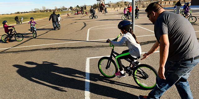 Elsiana Ruiz gets help learning to ride her bike from her father, Sinahy, at a playground in Aurora, Colorado. (Helen H. Richardson/The Denver Post via Getty Images)