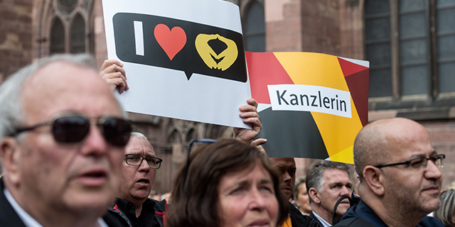 Supporters of German Chancellor Angela Merkel, top candidate for the conservative Christian Democratic Union party in the upcoming general elections, hold up posters to cheer for her during an election campaign event in Freiburg, southwestern Germany, on Sept. 18, 2017. (Patrick Seeger/AFP/Getty Images)