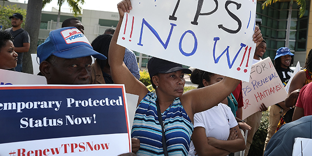People protest the possibility that the Trump administration may overturn Temporary Protected Status for Haitians in front of the U.S. Citizenship and Immigration Services office on May 13 in Miami. (Joe Raedle/Getty Images)
