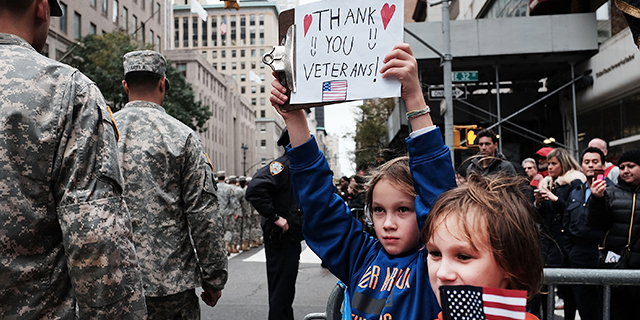 Gavin Kinney, left, and his brother Rigel hold up a sign at the New York City Veterans Day Parade on Nov. 11, 2015. (Spencer Platt/Getty Images)