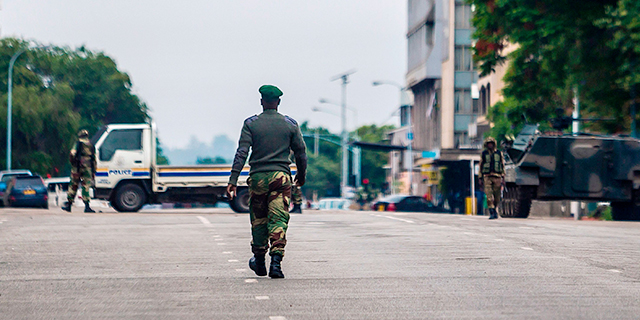 "Zimbabwean soldiers stand at an intersection as they regulate traffic in Harare on Nov. 15, 2017. Generals denied that the military had staged a coup but vowed on state television to target ""criminals"" close to President Robert Mugabe. (AFP/Getty Images)"