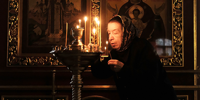 A woman lights a prayer candle at an Orthodox church in Moscow. (Spencer Platt/Getty Images)