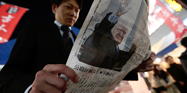 A man in Tokyo reads an extra edition of a newspaper featuring a report on the U.S. presidential election on Nov. 9, 2016. (Yuya Shino/Getty Images)
