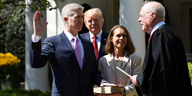Neil Gorsuch is sworn in as the newest member of the U.S. Supreme Court by Justice Anthony Kennedy in a White House Rose Garden ceremony on April 10, 2017. President Donald Trump, who appointed him, looks on as Gorsuch's wife, Louise, holds the Bible. (Xinhua/Yin Bogu via Getty Images)