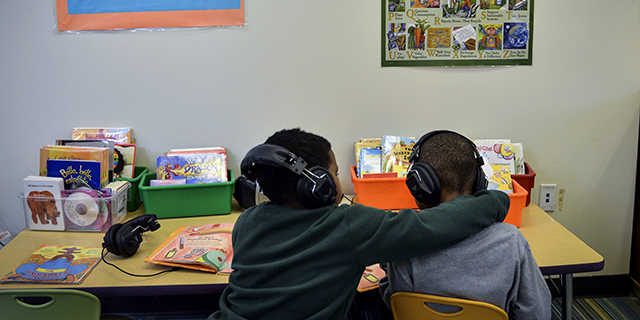 Adrian Malone, left, helps Gerald Elston adjust the volume on his headphones as the two listen to audiobooks at school in Washington, D.C. (Jahi Chikwendiu/The Washington Post via Getty Images)