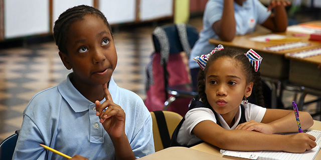 Nalani Reid ponders a math word problem on the first day of fourth grade in September 2016 at David A. Ellis Elementary School in Boston. Classmate Alanis Vega sits at right. (Pat Greenhouse/The Boston Globe via Getty Images)