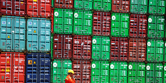 A worker walks by stacked containers at the port in Qingdao, China. (VCG/VCG via Getty Images)