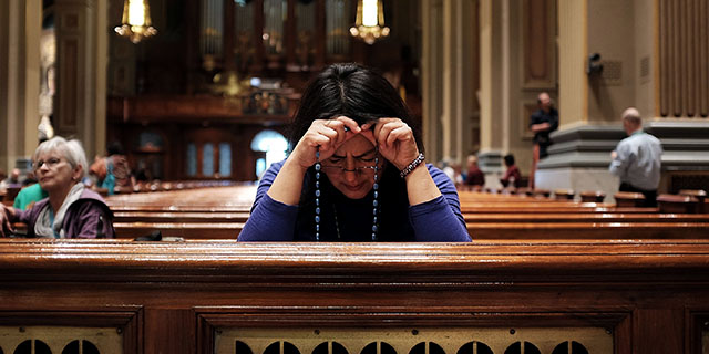 A woman prays at the Cathedral Basilica of Saints Peter and Paul in Philadelphia. (Spencer Platt/Getty Images)