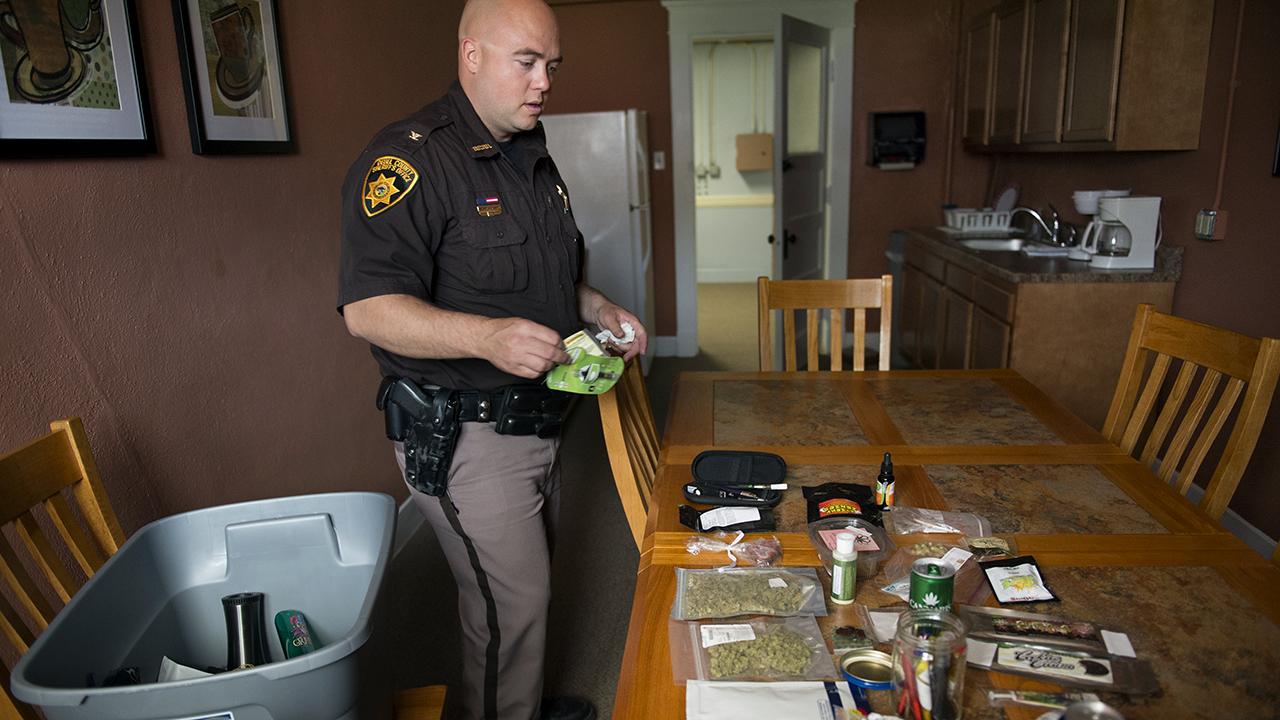 Deuel County's then-sheriff, Adam Hayward, displays confiscated marijuana items in Chappell, Nebraska, in 2014. (Nikki Kahn/The Washington Post via Getty Images)
