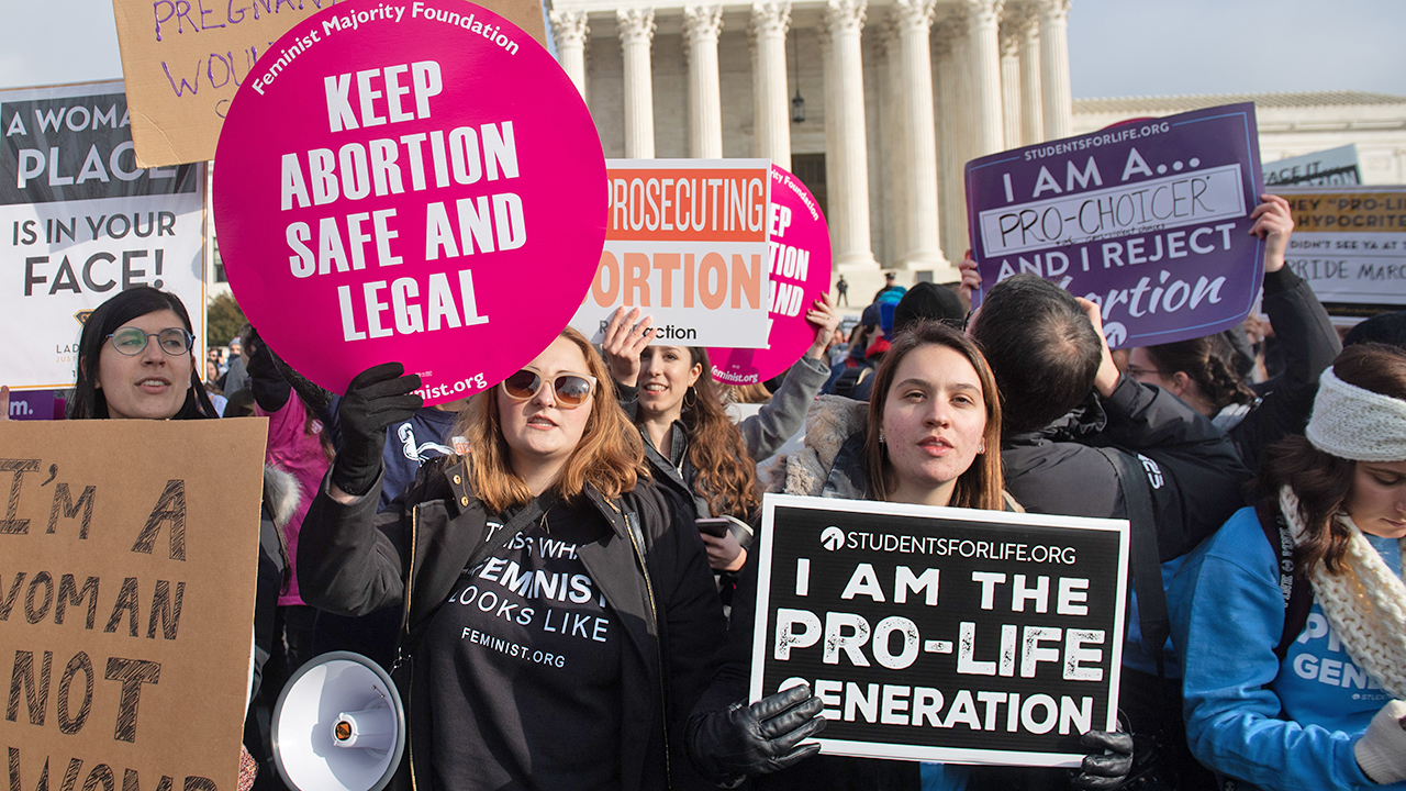 "Pro-choice activists hold signs alongside anti-abortion activists participating in the ""March for Life"" in Washington, DC, in January 2019. (SAUL LOEB/AFP via Getty Images)"