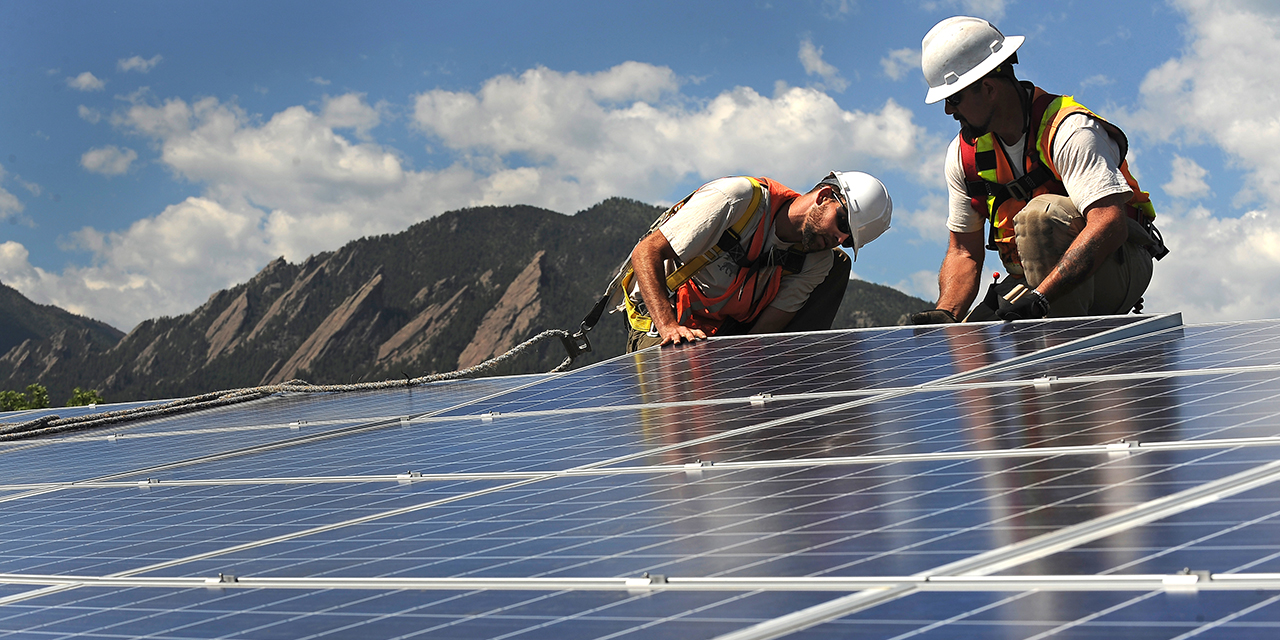 Workers install solar panels on a rooftop in Boulder, Colorado. (Helen H. Richardson/The Denver Post via Getty Images)