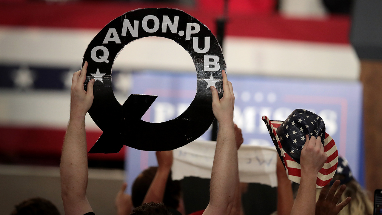 A person holds up a sign about QAnon at a political rally in Ohio in 2018. (Scott Olson/Getty Images)
