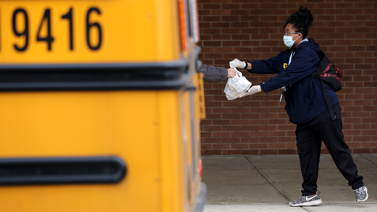 A school bus attendant in Gaithersburg, Maryland, hands out bags of food provided by a local food bank as part of a program to feed children while schools are closed for the COVID-19 outbreak. (Chip Somodevilla/Getty Images)