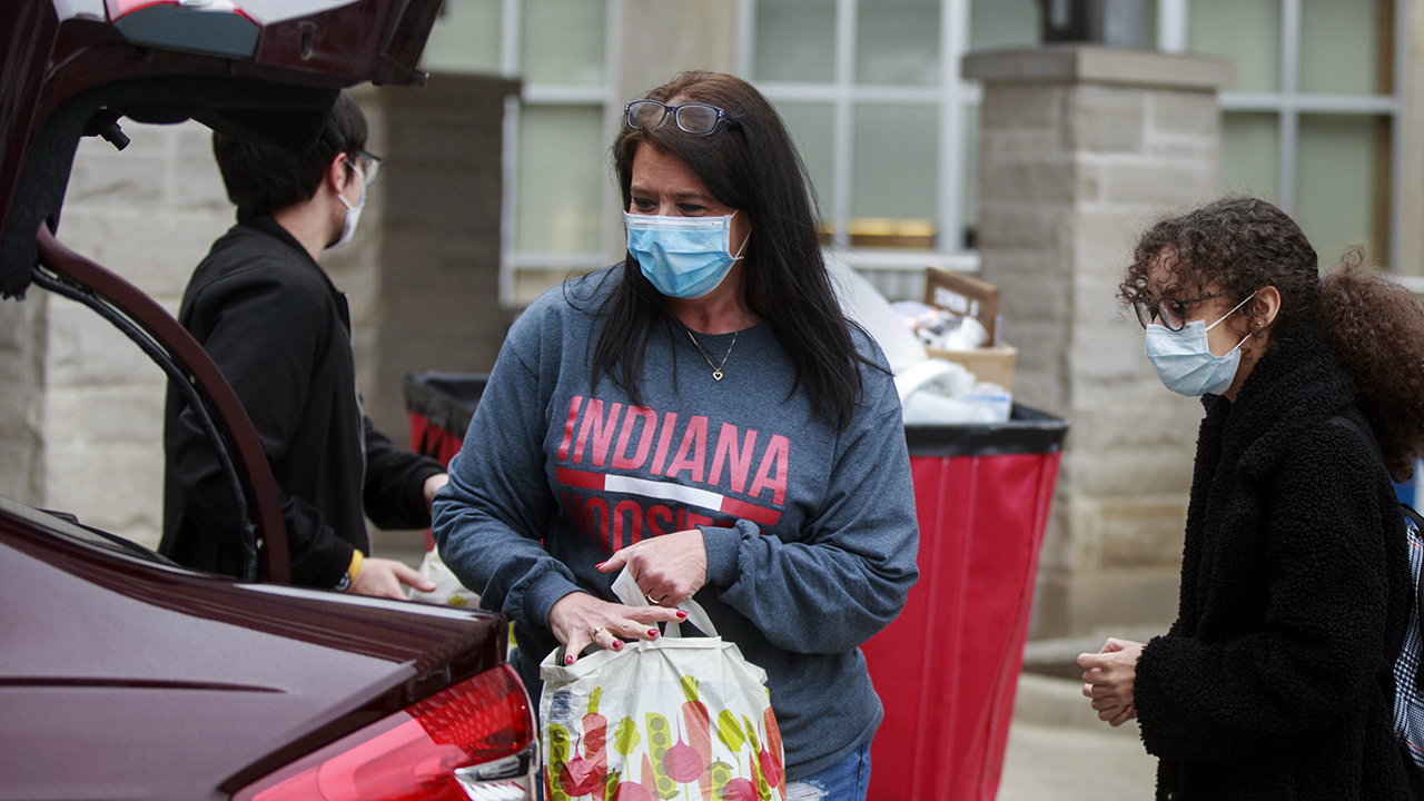 A mother in a mask helps move her daughter back home from a dorm at Indiana University on March 20. Students were told to vacate student housing due to the coronavirus emergency. (Jeremy Hogan/SOPA Images/LightRocket via Getty Images)