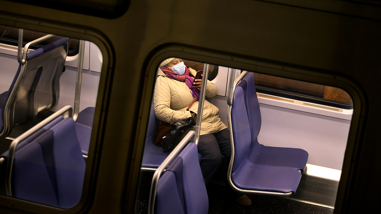 A passenger riding Metro in Washington, D.C., checks her cellphone on March 25. (Chip Somodevilla/Getty Images)