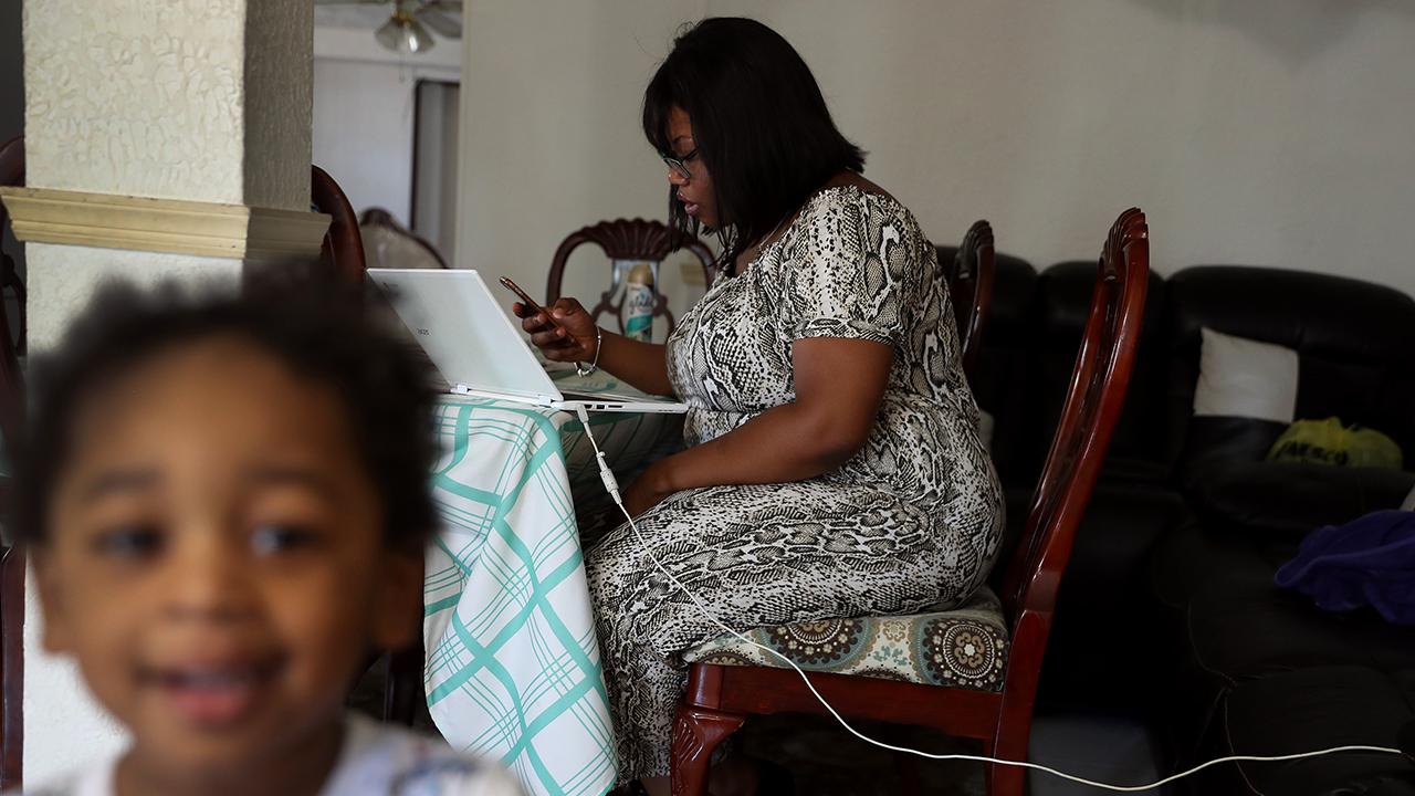 A woman in Hollywood, Florida, fills out an unemployment application online after being laid off from her job at the nearby airport. (Joe Raedle/Getty Images)
