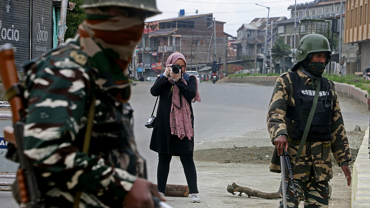 Photojournalist Masrat Zahra takes pictures near a temporary checkpoint in Srinagar, in Indian-controlled Kashnmir, on April 21. (Faisal Khan/Anadolu Agency via Getty Images)