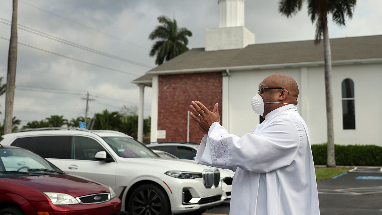 A religious leader greets parishioners arriving for Easter worship in Florida. In order to observe social distancing guidelines, members of the congregation met in the parking lot and watched a Facebook Live streaming of the service taking place inside the church. (Joe Raedle via Getty Images)