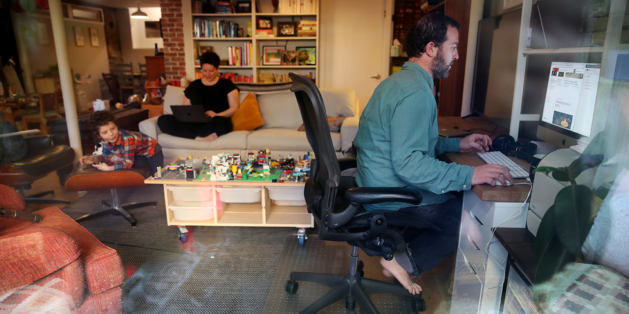 Parents in Boston work at home on April 14 during the coronavirus stay-at-home advisory as their son, 5, entertains himself. (Craig F. Walker/The Boston Globe via Getty Images)