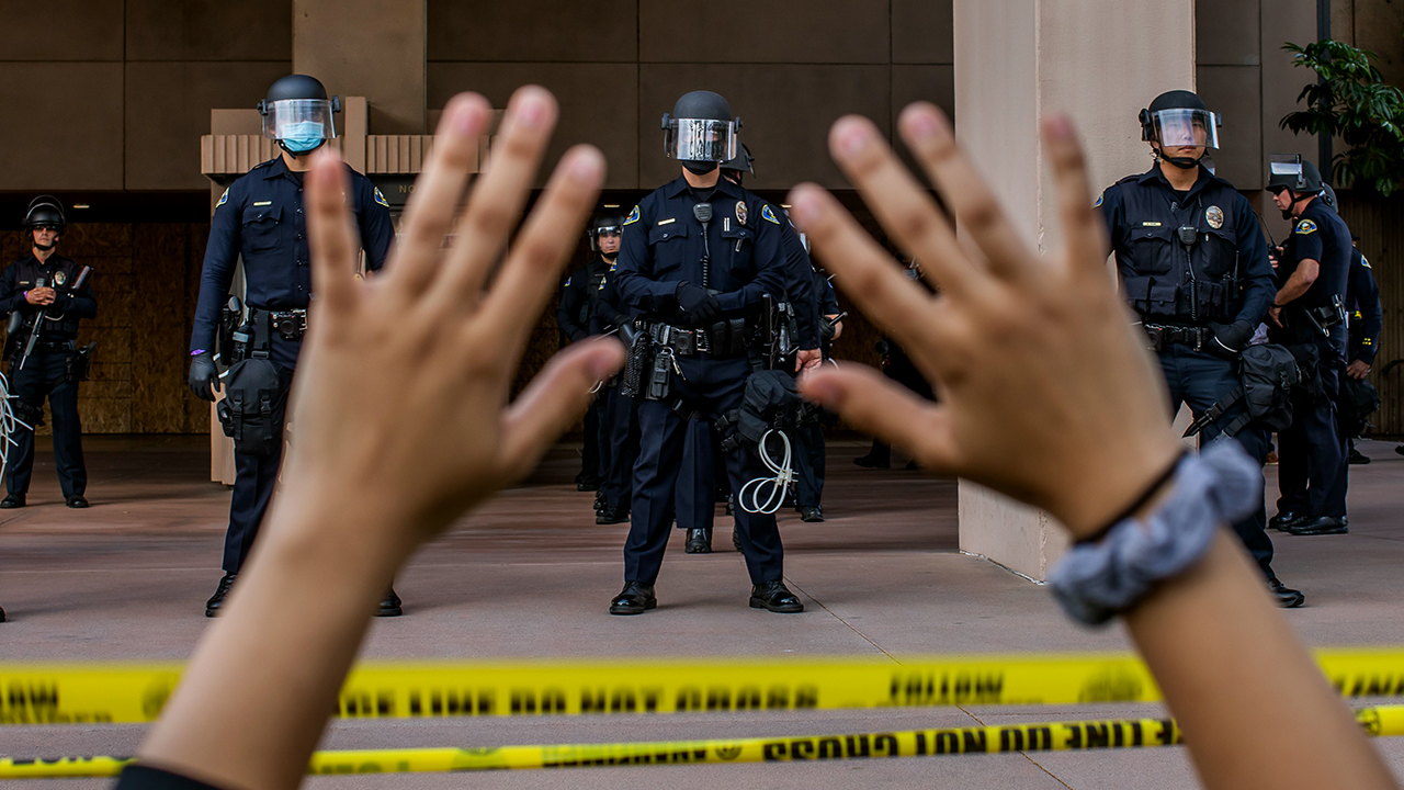 A demonstrator holds her hands up while kneeling in front of police at City Hall in Anaheim, California, on June 1, 2020, during a peaceful protest over the death of George Floyd. (Apu Gomes/AFP via Getty Images)