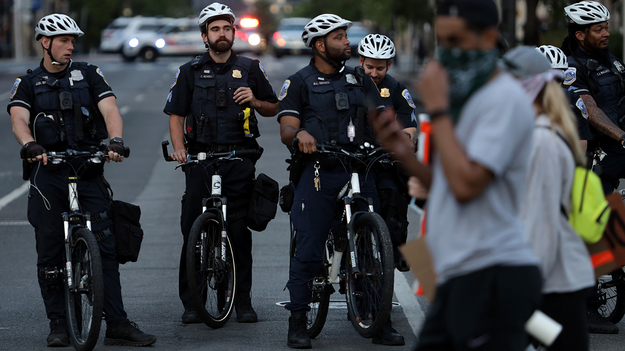 Metropolitan police officers in Washington, D.C., watched protesters leave a rally on June 2, 2020, in Washington, D.C., after the death of George Floyd, a black man who died in police custody in Minneapolis on May 25. (Alex Wong/Getty Images)