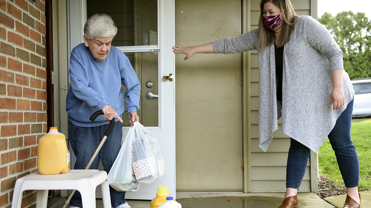 Shannon Flemming delivers groceries to Joyce Herzog in Kurtztown, Pennsylvania, on April 8 as part of a community effort to allow seniors to stay at home during the COVID-19 outbreak. (Lauren A. Little/MediaNews Group/Reading Eagle via Getty Images)